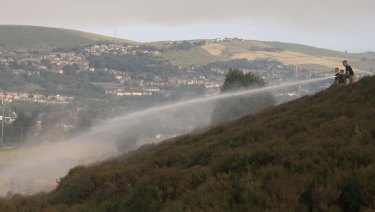 Firefighters work to damp-down land on Saddleworth Moor as a wildfire threatens a nearby village.