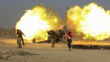 Iraqi security forces and allied Popular Mobilization forces fire artillery during fight against Islamic State militants in Fallujah.