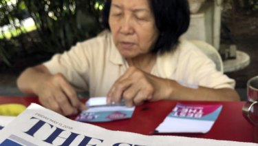 A news vendor counts her money near a stack of newspapers with a photo of Trump, right, and Kim on its front page in Singapore.