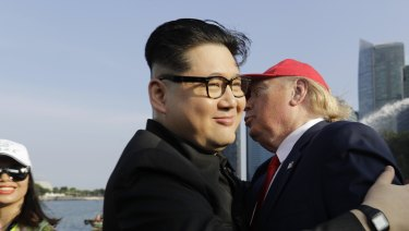 Kim Jong-un and Donald Trump impersonators Howard X, center, and Dennis Alan, right, embrace in Merlion Park in Singapore last Friday.