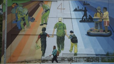 """A woman walks pass a mural titled """"Migration is not a game of hop scotch,"""" in San Salvador, El Salvador. For now the outrage caused by the policy of separating children from their parents is likely to deter more Central Americans from leaving home, said Andrew Selee, president of the Migration Policy Institute."""
