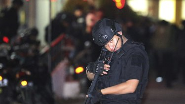 An Indonesian police officer stands guard in front of an apartment building after an explosion in Sidoarjo, East Java.
