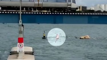 The man lands in the water after jumping from the train on the Fremantle bridge.