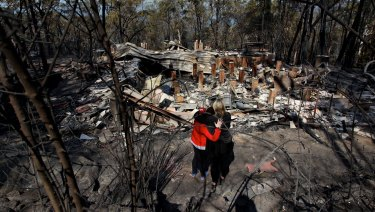 Amy Hubbard (left) with her mother, Catherine and the ruins of their home in Buena Vista Road, Winmalee, that was destroyed in a bushfire fires in the Blue Mountains on October 18, 2013.