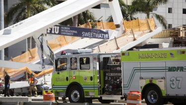 Emergency personnel responds to the collapsed pedestrian bridge in Florida.