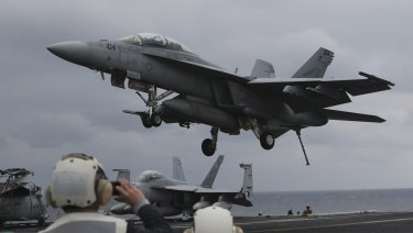 US Navy's F/A-18 Super Hornet fighter approaches the deck of the USS Carl Vinson.