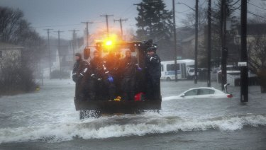 A Marine dive team is transported along a flooded Sea Street, Boston, by front-end loader on Friday.