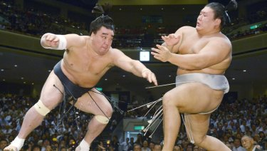 Mongolian sumo grand champion Harumafuji, left, pushes opponent Takanoiwa out of the ring to win their bout at the Autumn Grand Sumo Tournament in Tokyo in 2016.