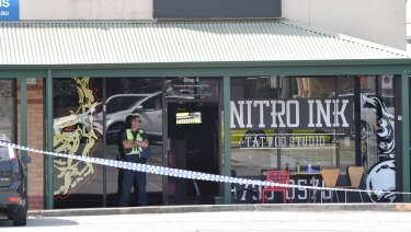 A police officer guards the Nitro Ink tattoo parlor after February's shooting.