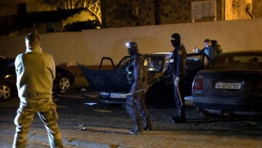 French Police officers search a car during a raid in Carcasona following an incident in Trebes, on Friday.
