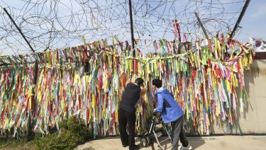 A man hangs a ribbon carrying messages wishing the reunification and peace of the two Koreas on the wire fence near the border.