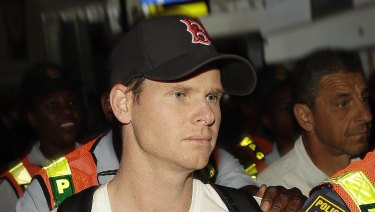 Steve Smith was escorted by police officers on departure in Johannesburg.