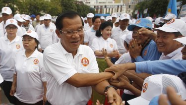Cambodian Prime Minister Hun Sen, centre, greets supporters.