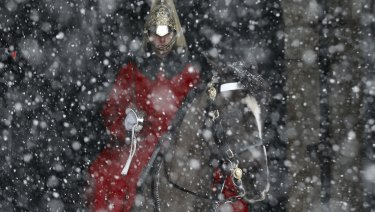 Snow falls on a soldier from the mounted Household Cavalry near Horseguards Parade in central London.