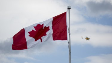 A helicopter flys past a Canadian flag in Niagara Falls, Ontario, Canada.