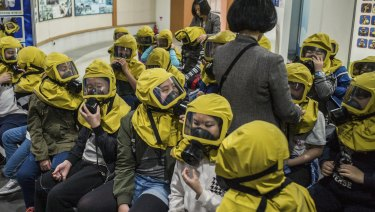 South Korean children learn to use gas masks.