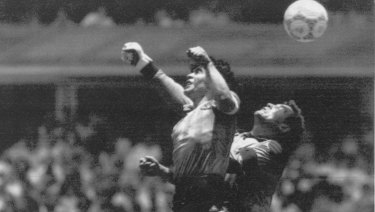 "Diego Maradona (left) beats England goalkeeper Peter Shilton to a high ball and scores the ""Hand of God"" goal off his left hand."
