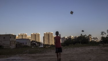 A boy flies a kite in an empty lot in front of the Ilha Pura property, 3604 empty luxury apartments used by more than 18,000 athletes during the Olympic games.
