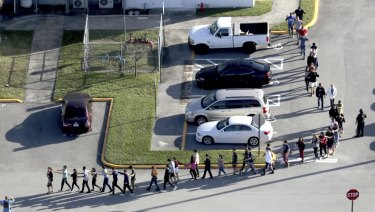 Students are evacuated by police from Marjory Stoneman Douglas High School following the shooting.