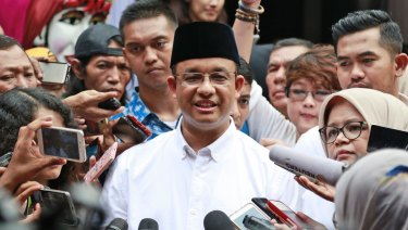Anies Baswedan, centre, is mobbed by the press after casting his vote in Gubernatorial elections last year.
