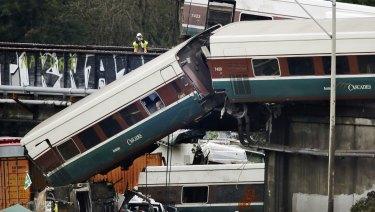 An investigator takes photos off a railroad bridge at the scene of where an Amtrak train derailed in DuPont, Washington.