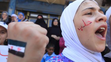 "A girl with ""Aleppo"" written on her face shouts slogans during an anti-government demonstration in Bennish, on the outskirts of Idlib province, in August 2012."