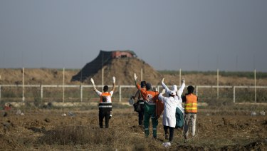Palestinian medics raise their hands up while walking towards the Israeli side of the border with Gaza to evacuate a injured protester on Monday.