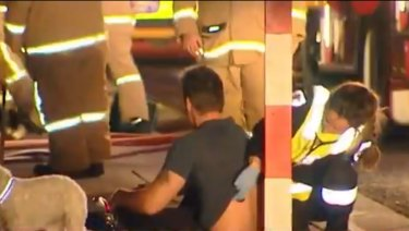 A man being treated by paramedics following a fire in Frankston South.