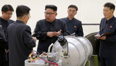 North Korean leader Kim Jong-un examines an explosive device.
