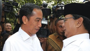 Indonesian President Joko Widodo, left, is embraced by his political rival Prabowo Subianto in 2014.