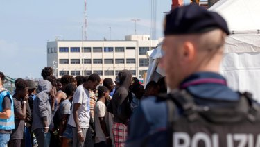 Migrants line-up after disembarking from a different vessel at the Reggio Calabria harbour on Saturday.