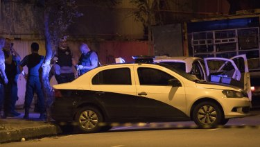 Police officers work next to the car in which Marielle Franco was travelling.
