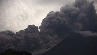 Volcan de Fuego, or Volcano of Fire, blows outs a thick cloud of ash.