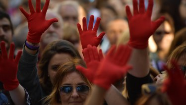 Women wearing red gloves while protesting at Plaza del Ayuntamiento square after three of five men granted bail after being acquitted of gang rape leave Pamplona's penitentiary, in Pamplona, northern Spain.