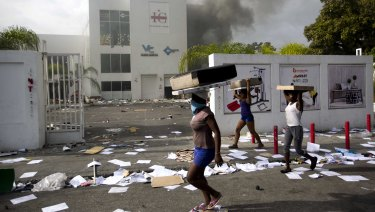 People carry items from a market during protests over a fuel price increase in Port-au-Prince, Haiti.
