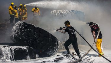 Israeli firefighters extinguish tractor tires in a farmland set on fire by a kite with attached burning cloth launched from Gaza on the Israeli side of the border, Tuesday, May 15, 2018. Israel faced a growing backlash Tuesday and new charges of using excessive force, a day after Israeli troops firing from across a border fence killed dozens of Palestinians and wounded more than 2,700 at a mass protest in Gaza. (AP Photo/Tsafrir Abayov)