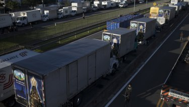 A bicyclist pedals past trucks partially blocking a road, that connects the cities Rio de Janeiro and Teresopolis, in Brazil.