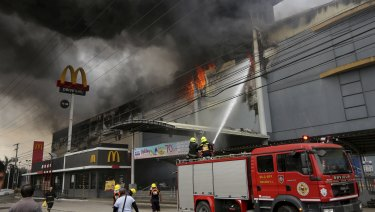 Firemen battle a fire that rages at a shopping mall in Davao city, southern Philippines.