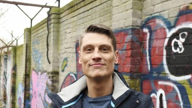 Local historian Christian Bormann stands in front of a piece of the Berlin Wall in Berlin.
