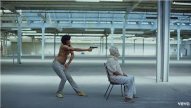 Childish Gambino stands behind Calvin the Second with a gun.