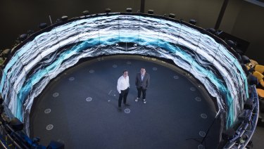 Dr Eric Thrane (left) and Dr Rory Smith at Monash University surrounded by an artist's impression of the background hum of gravitational waves permeating the Universe.