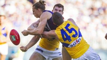 Crunched: Fremantle's Nat Fyfe gets double-teamed by West Coast defenders.