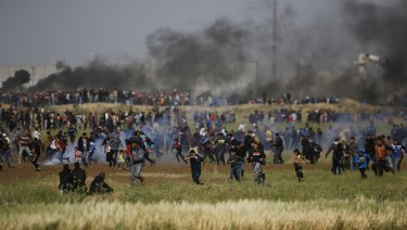 Palestinian protesters run from tear gas after Israeli troops fired canisters at the crowd.