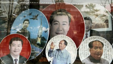 Porcelain plates featuring portraits of former Chinese leader Mao Zedong, bottom second right and bottom right, and Chinese PresidentXi Jinping are displayed in a shop window in Beijing.