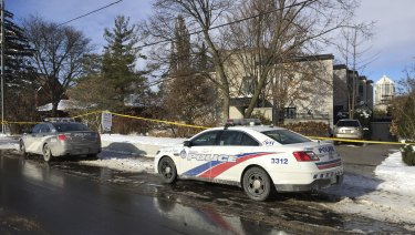 Police cars are parked outside the home of billionaire Barry Sherman in Toronto.
