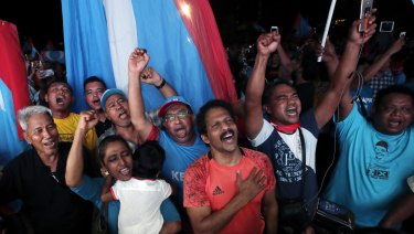 Opposition party supporters cheer and wave their party flags on election night.