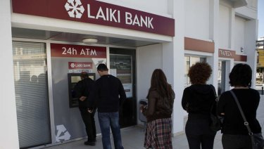 Badly mishandled: People queue to use an ATM outside a Laiki Bank branch in Larnaca, Cyprus.