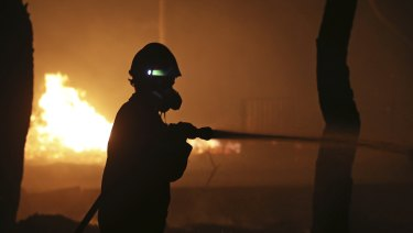 A firefighter sprays water on the fire in the town of Mati, east of Athens.
