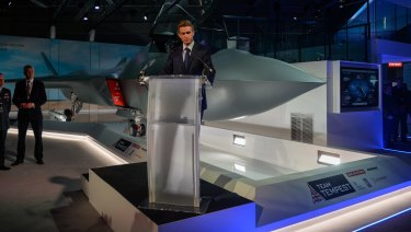 Gavin Williamson, UK defence secretary, stands at a lectern as a full-size model of a Tempest, UK's new fighter jet, is unveiled on the opening day of the Farnborough International Airshow 2018.