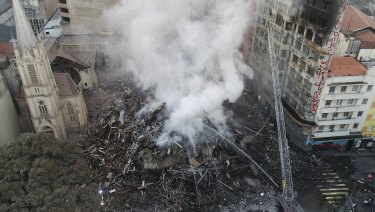Firefighters work in the the rubble of a building that caught fire and collapsed in Sao Paulo, Brazil.